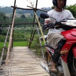 Vietnam motorbike tours, Vietnam motorcycle tours. Crossing a local bamboo bridge on a scooter.